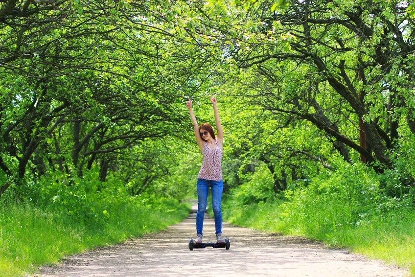 Frau fährt auf einem Waldweg mit einem Self Balancing Scooter